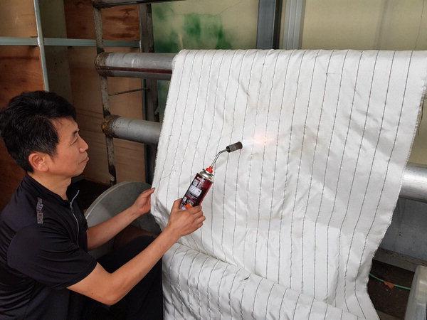 ▲ 화염전파 차단용 방화스크린 원단의 방염성 테스트 장면. /한국세라믹기술원